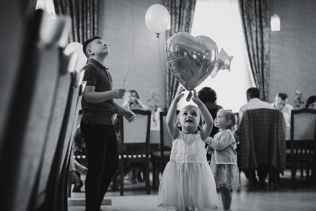 Czarno-białe zdjęcie pokazujące dzieci bawiące się balonami