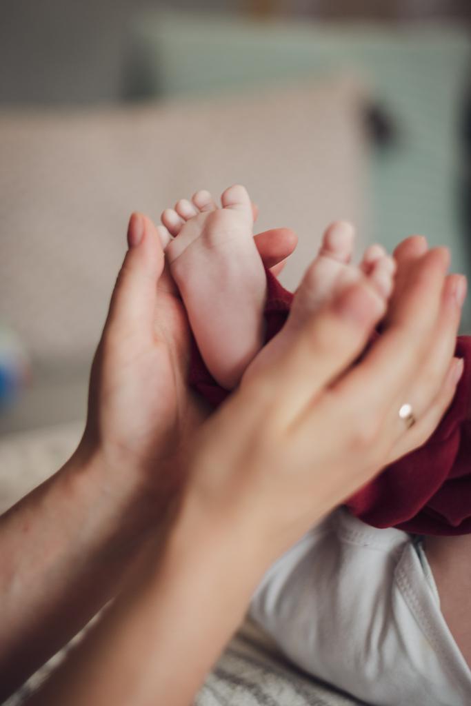 Mama trzymająca niemowlęce stopy