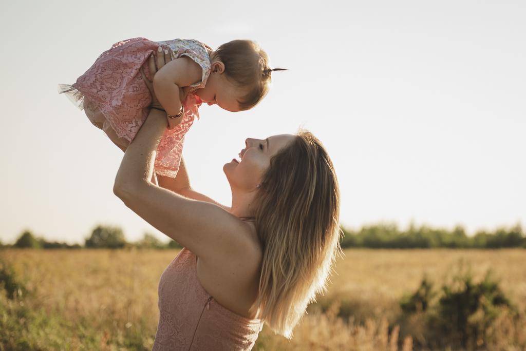 Szczęśliwa mama bawi się z dzieckiem podczas sesji rodzinnej