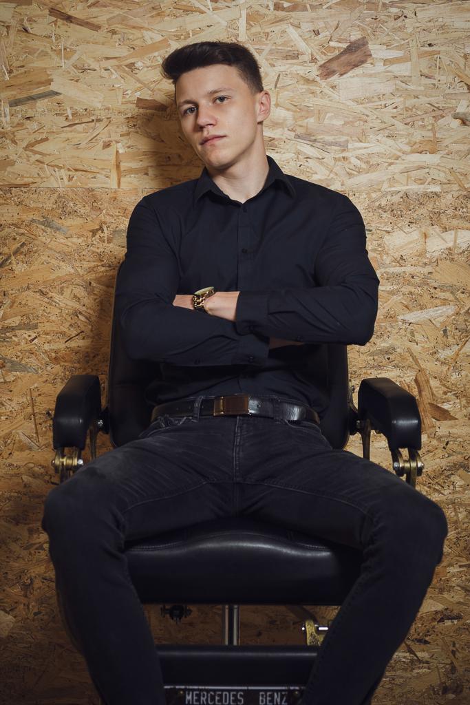 Portret biznesowy fryzjera na fotelu fryzjerskim