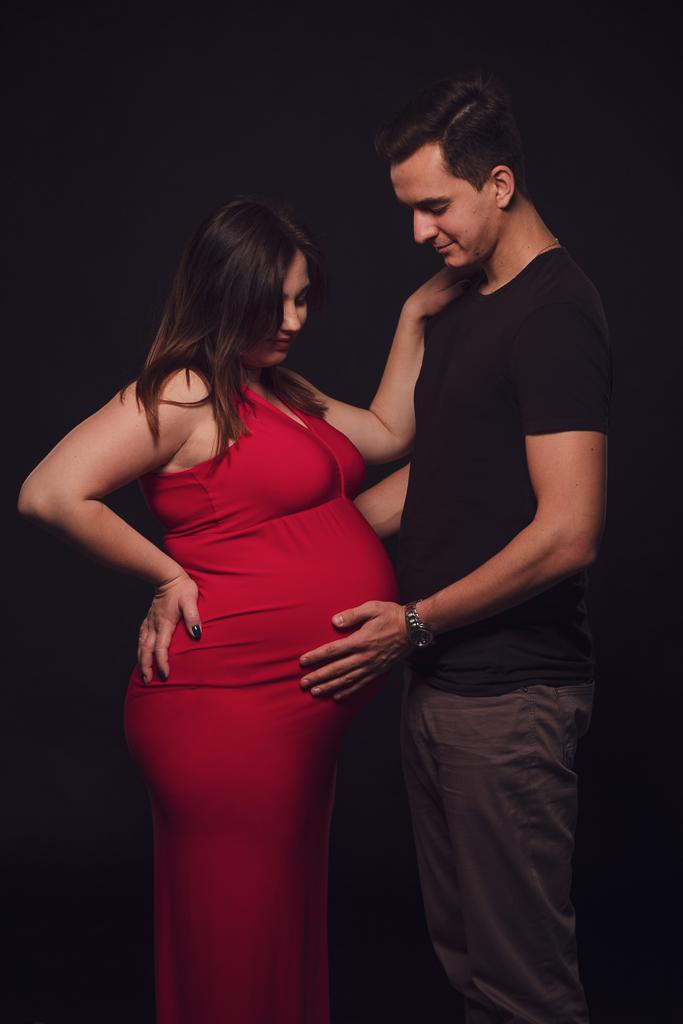 Studyjna sesja ciążowa, para na czarnym tle