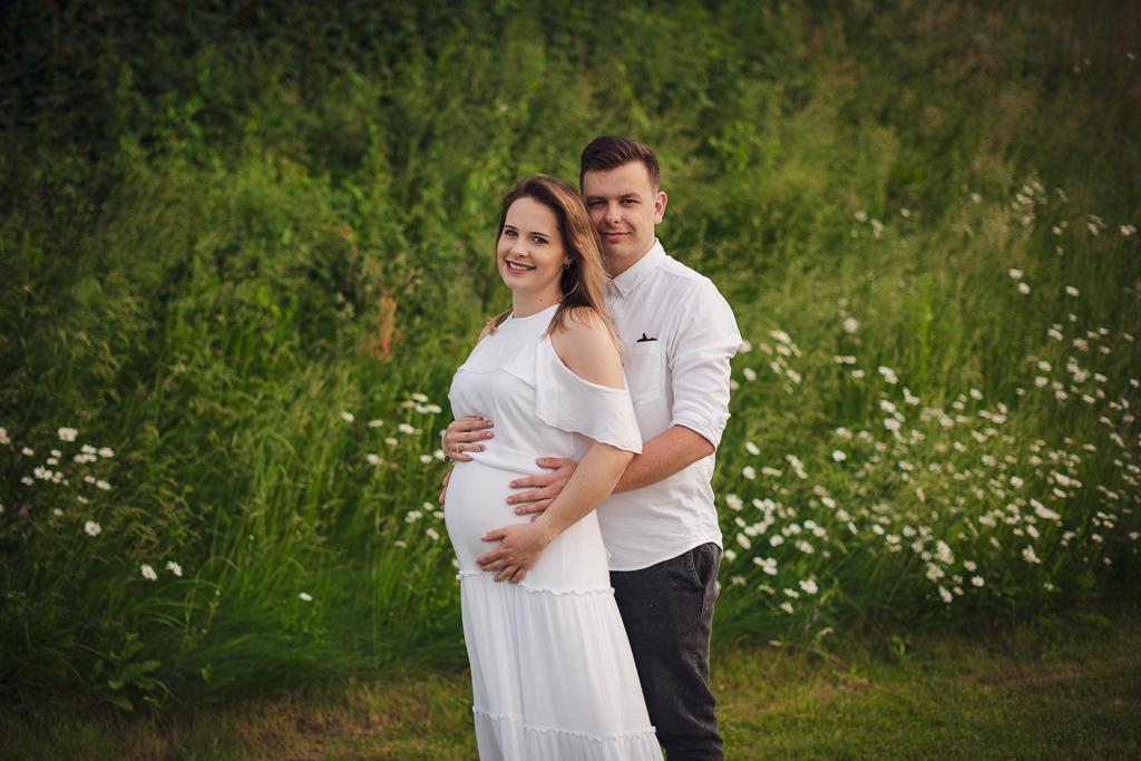 Sesja ciążowa na tle zielonej trawy