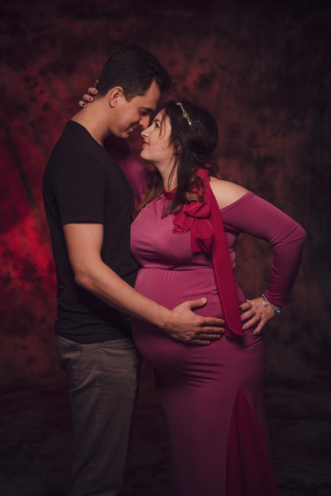 Studyjna sesja ciążowa, uśmiechnięta para